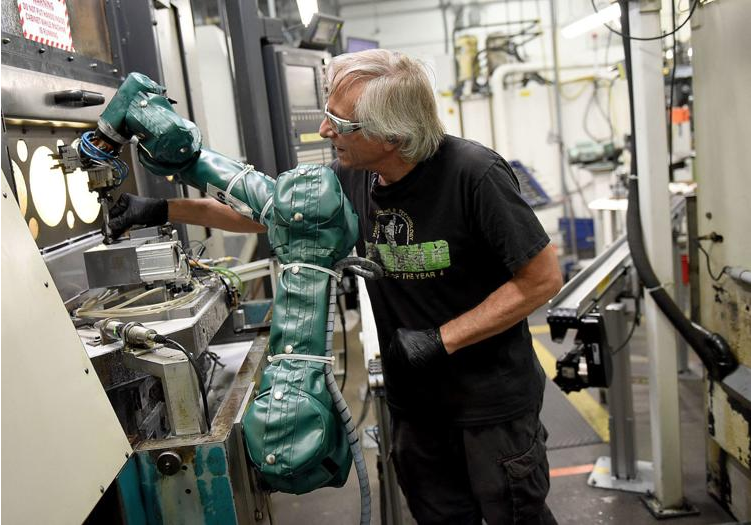 man working with robot wearing a protective suit